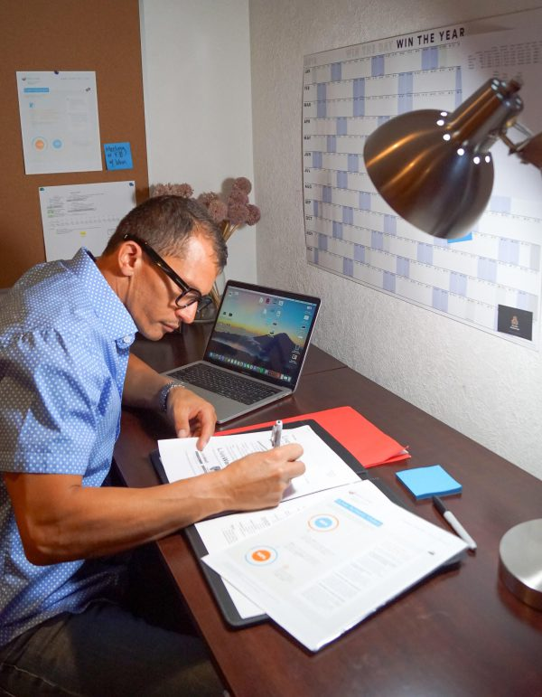 Man working at a desk with laptop and notebook while a bright NorbFOCUS bulb illuminates the area