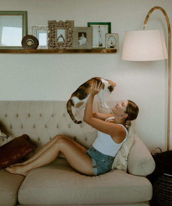 Woman holding a cat while sitting on sofa, underneath a NorbSMILE full spectrum light bulb
