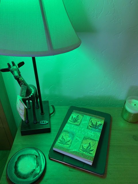 A bedside table with a book and candle underneath a lamp using the green light NorbRELIEF LED