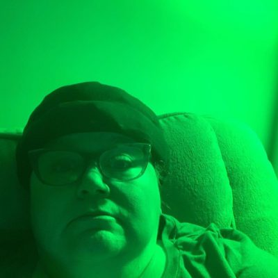 Melanie Grossi sitting under the NorbRELIEF green migraine light