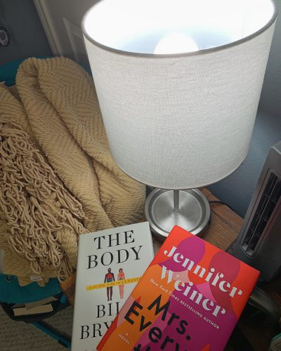 Books underneath a bedside lamp using the NorbSLEEP wellness LED bulb