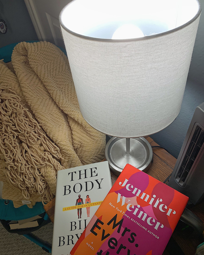 Books underneath a bedside lamp using the NorbSLEEP wellness LED bulb